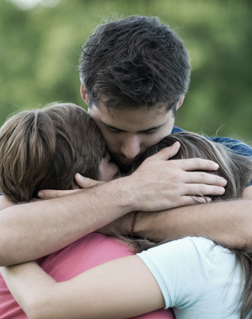 father hugging his children - - Brass Tacks Recovery - Intervention and Family Support Services